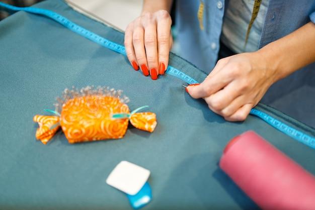 Швея измеряет тканевый материал, вид сверху, текстильная мастерская. женщина работает с тканью для шитья, портной на рабочем месте, портниха