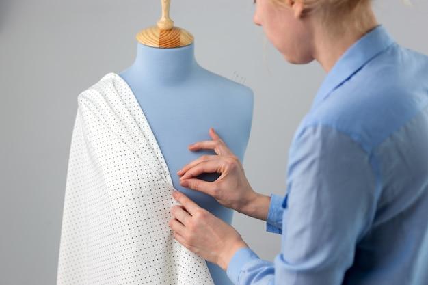 Швея измеряет красивую ткань на синем портновском манекене в своей мастерской.