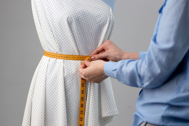 彼女のワークショップで青い仕立てのダミーの美しい生地を測定する針子。