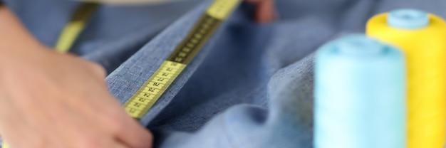 바느질 작업장에서 센티미터 테이프로 드레스의 칼라를 측정하는 재봉사. 중소 기업 개발 개념