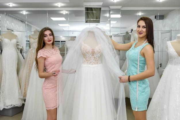 Швея или свадебный консультант помогает невесте в салоне