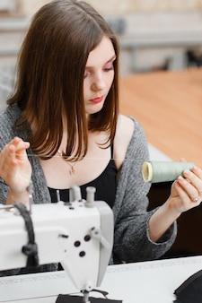 Seamstress preparing for work at sewing machine.