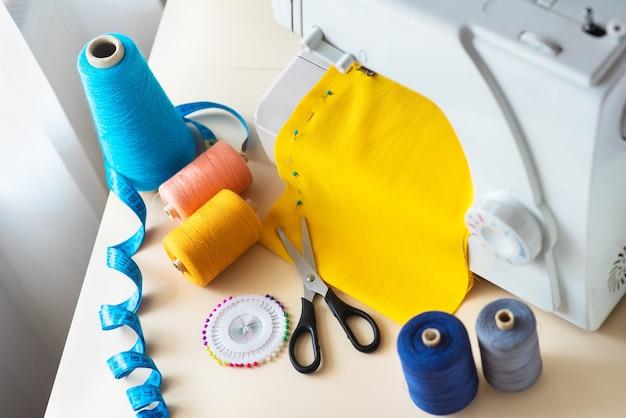 재봉사의 직장. 직장에서 전문 재봉틀입니다. 재봉틀은 재봉을 위해 밝은 직물, 미터 및 유색 실을 재봉합니다.