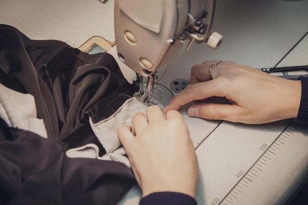 Швея шьет одежду - модную куртку из бархата на швейной машине в своей мастерской, вид сверху крупным планом.