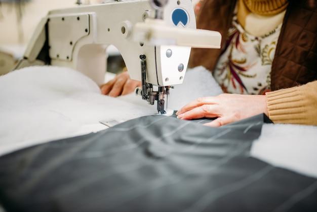 Швея сшивает ткань на швейной машине. пошив одежды на швейной фабрике, рукоделие