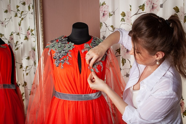 The seamstress sews lace and beads to the dress