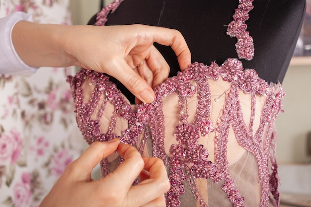 The seamstress sews lace and beads to the pink dress