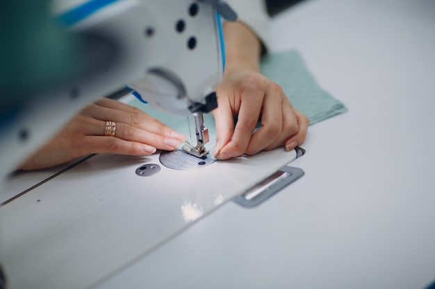 Seamstress sews on sewing machine in factory