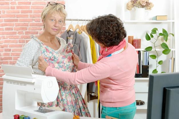 Швея показывает модель платья