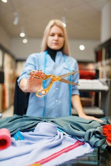 Швея показывает ножницы, текстильная мастерская. женщина держит инструменты для шитья, портной на рабочем месте, пошив одежды