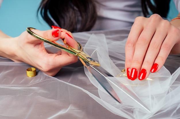 赤いマニキュアの針子仕立ての洋裁の女性の手は、はさみを保持し、スタジオのテーブルで生地をカットします。