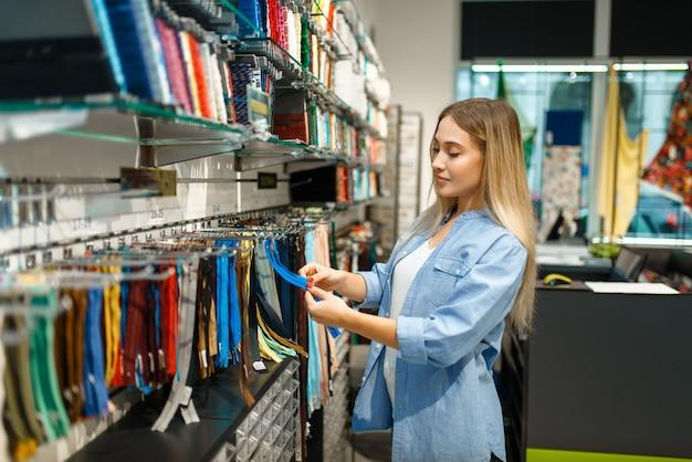 Швея берет молнию в текстильной мастерской. женщина, выбирающая ткань для шитья, портной на рабочем месте, портниха