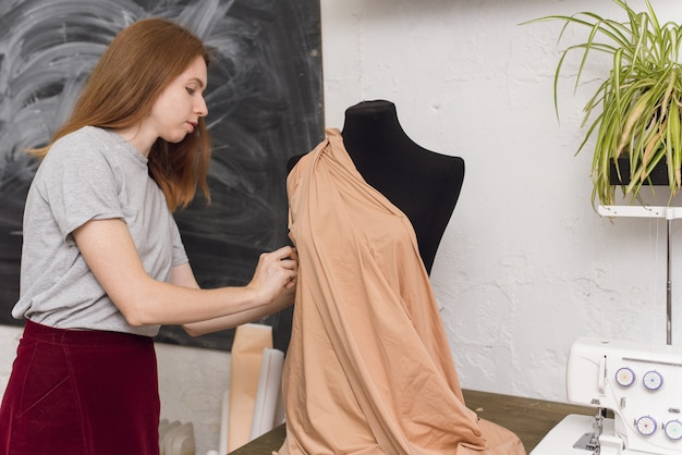 Seamstress tries on fabric on a black mannequin in a sewing workshop. the designer designs a dress from beige fabric and creates clothes.