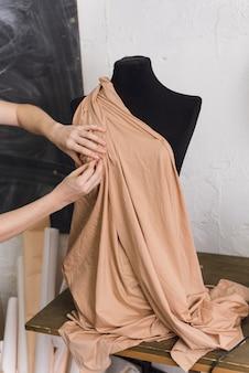 재 봉사는 바느질 워크숍에서 검은 마네킹에 직물을 시도합니다. 디자이너는 베이지 색 패브릭으로 드레스를 디자인하고 옷을 만듭니다.