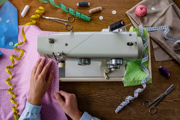 Seamstress using a sewing machine and various sewing accessories for clothes production