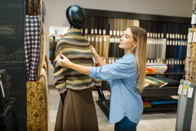 Швея с тканью на манекен в текстильном магазине. женщина выбирает материал для шитья, портной в магазине, портниха