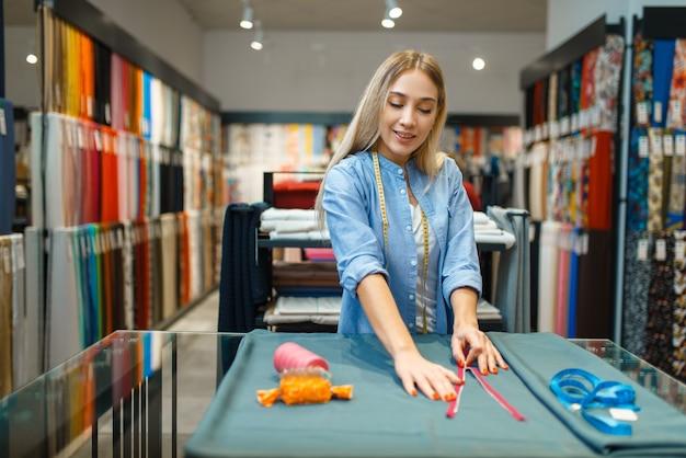 Швея с рулеткой и застежкой-молнией, текстильная мастерская. женщина работает с тканью для шитья, портной на рабочем месте, портниха