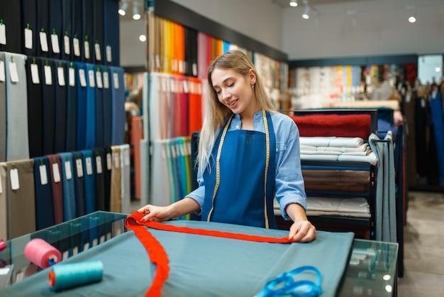 Швея с лентой измеряет крупный план ткани в магазине текстиля. полка с тканью для шитья