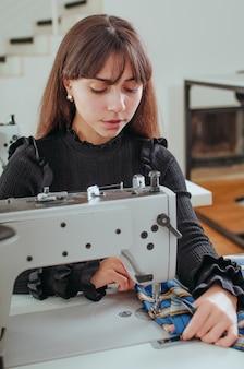 Швея работает на швейной машине на рабочем месте портнихи