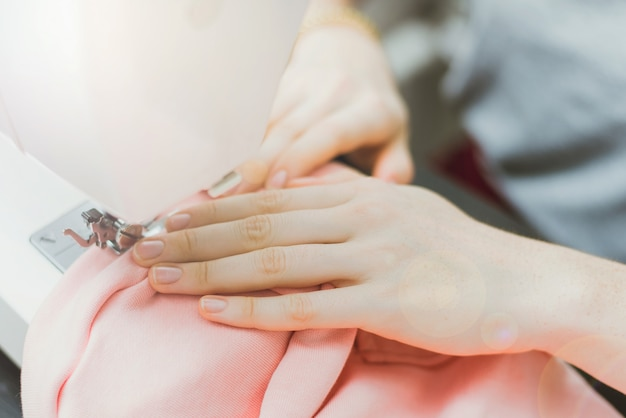 Seamstress works on a sewing machine. the girl sews and holds a pink cloth
