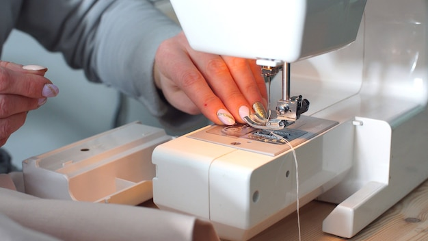 Seamstress works on a sewing machine in her workshop