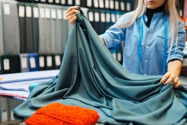 Швея работает с тканью, текстильная мастерская. женщина держит ткань для шитья, портной на рабочем месте, пошив