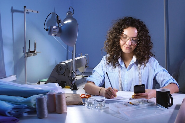 Seamstress writing notes in diary at the table.