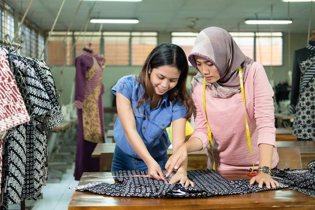 Швеи и супервайзеры измеряют ткань линейкой перед тем, как шить.