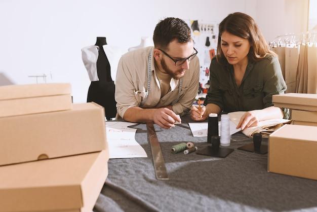 Seamstressesチームは新しい服を着てクライアントにパッケージを出荷する準備ができています