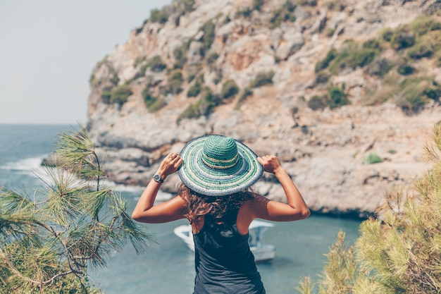 Женщина смотря seand держа ее шляпу в seashore в черной рубашке во время дневного времени