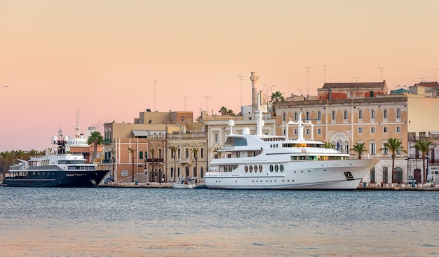Морской порт и корабли в городе бриндизи на закате, летом в апулии. италия