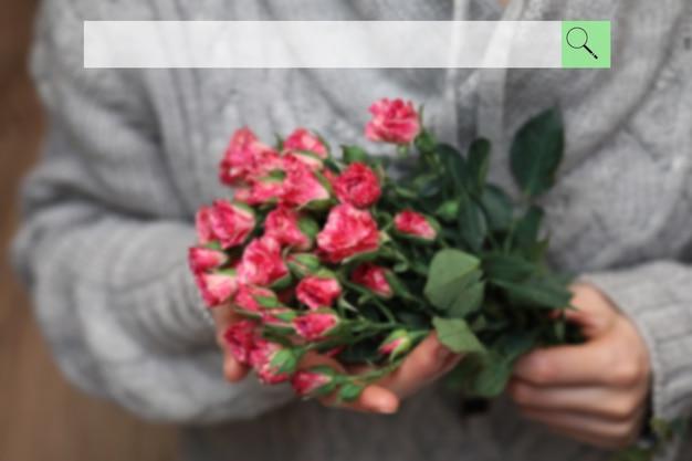 Панель поиска на фоне размытого букета куста роз в женских руках