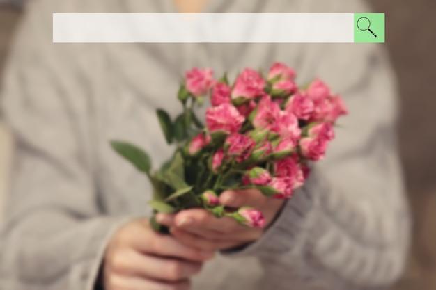 여성 손에 장미 덤불의 흐릿한 꽃다발의 배경에 검색 창