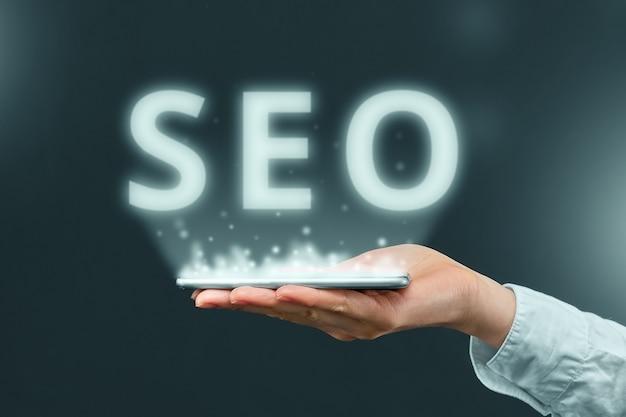 Концепция поисковой оптимизации над смартфоном в руке бизнесмена