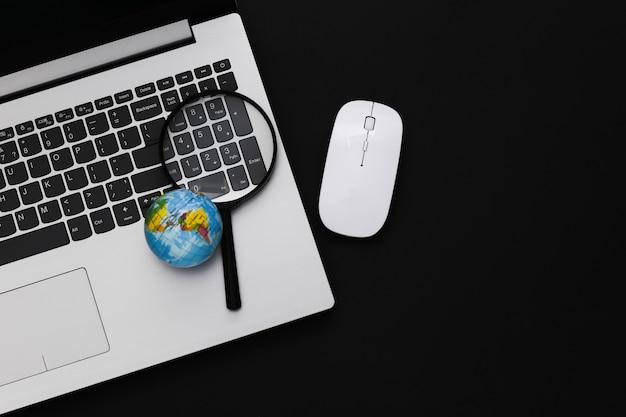 情報を検索します。 pcのマウス、拡大鏡、黒い背景の上の地球とラップトップ。上面図