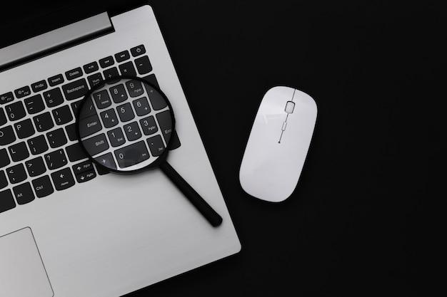 情報を検索します。 pcマウス、黒の背景に拡大鏡を備えたラップトップ。上面図