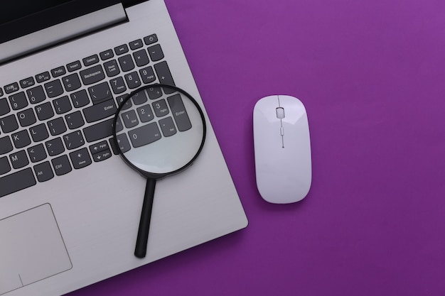 情報を検索します。 pcマウス、紫色の背景に拡大鏡を備えたラップトップ。上面図