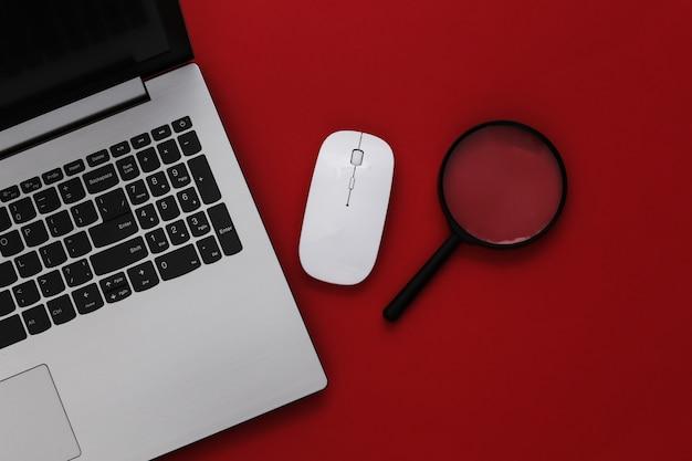 情報を検索します。 pcマウス、赤い背景の拡大鏡とラップトップ。上面図