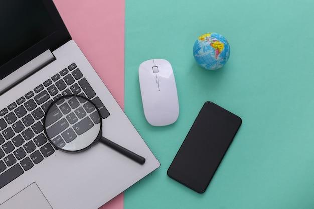 情報を検索します。 pcのマウス、拡大鏡、スマートフォン、ピンクブルーの背景に地球儀を備えたラップトップ。上面図