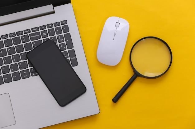 情報を検索します。 pcのマウス、スマートフォン、黄色の背景に拡大鏡を備えたラップトップ。上面図