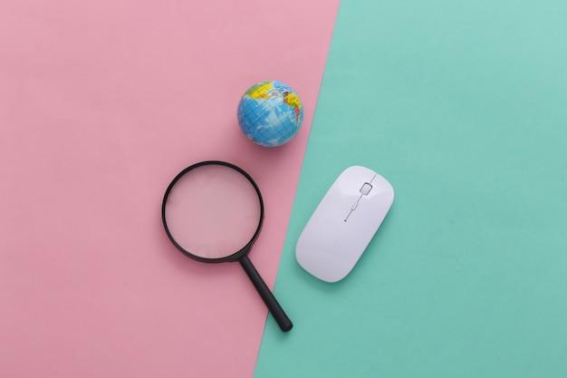 情報を検索します。 pcマウス、拡大鏡、ピンクブルーのパステルカラーの背景に地球儀。上面図