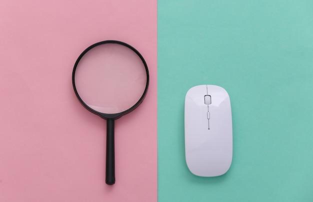 情報を検索します。 pcマウス、ピンクブルーのパステルカラーの背景に拡大鏡。上面図