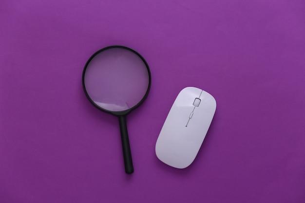 情報を検索します。 pcマウス、紫色の背景に拡大鏡。上面図