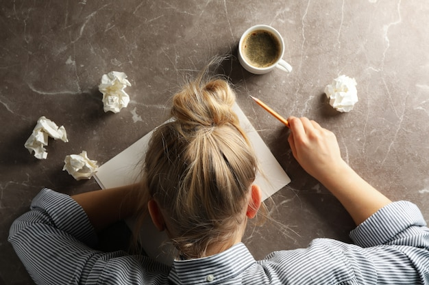 In search of inspiration. girl, paper balls and cup of coffee on grey background, top view