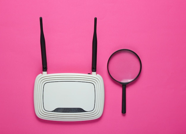Search on the internet. wifi router and magnifier on a pink paper