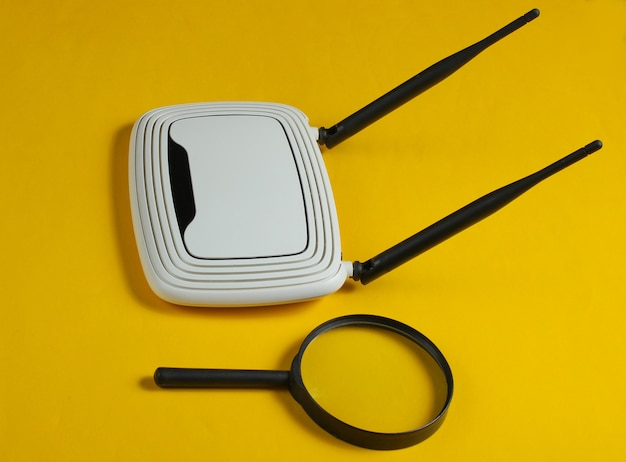 Search on the internet. wifi router and magnifier on yellow paper