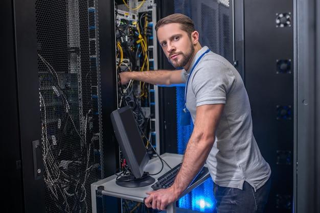 Поиск, решение. серьезный умный молодой бородатый мужчина со значком работает в серверной комнате, проверяя кабель