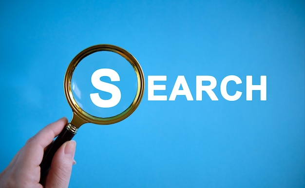 Search - text with a magnifying glass on a blue background