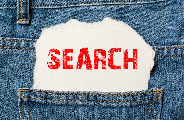 Search on white paper in the pocket of blue denim jeans