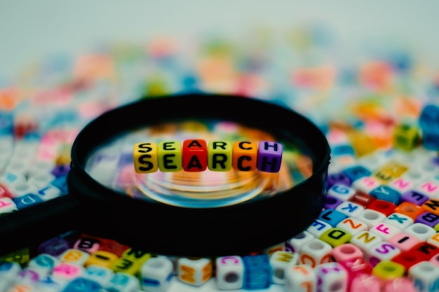 Search word on the magnifying glass with alphabet letter beads